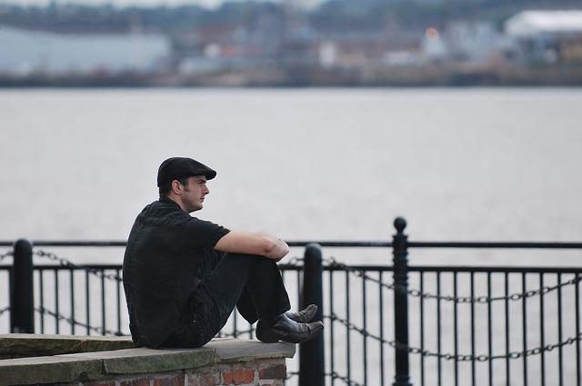 画像:海辺で悩む男性
