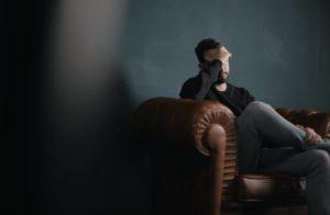 画像:ソファで悩む男性